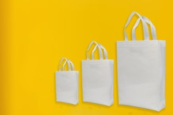 White Non Woven shopping ECO bags Isolated on yellow background with copy space for banner and text logo