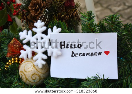 White note with hello December text and Christmas decorations on a blue table