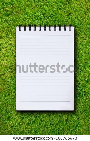 White notebook in green grass background