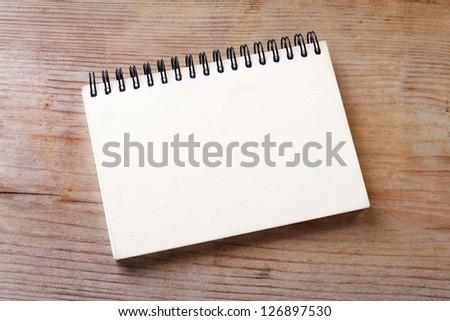 White notebook on wooden ground/notebook/paper