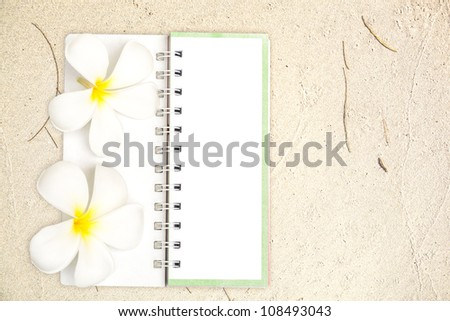 White notebook with white Frangipani flower on the sand