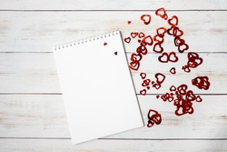 White notepad and many small hearts. Valentine's Day holiday card. Valentines day concept. Flat lay, top view, copy space.