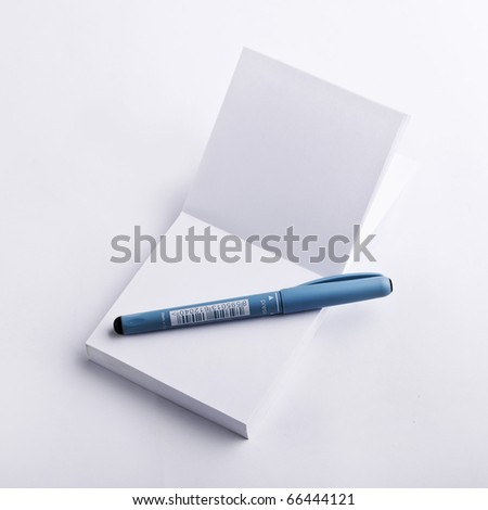 White notepad with stylish blue pen