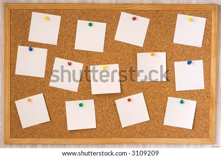 White notes pinned ( with pin ) to cork board ( notice corkboard  )