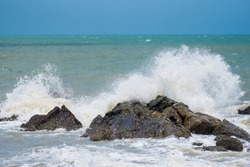 White ocean waves crashing over coastal sea rocks in summer.Thailand