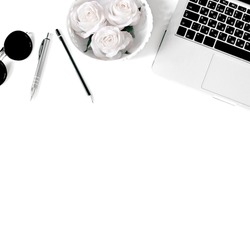 White office desk frame with laptop keyboard and supplies. Laptop, notebook, pen, clips, pencil, roses and office supplies on white background. Flat lay, top view, mockup