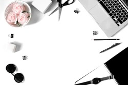 White office desk frame with laptop keyboard and supplies. Laptop, notebook, pen, roses, sunglasses, clips, pencil, scissors, watch and office supplies on white background. Flat lay, top view, mockup