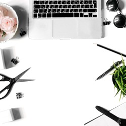 White office desk frame with laptop keyboard and supplies. Laptop, notebook, pen, roses, sunglasses, clips, plant, scissors, watch and office supplies on white background. Flat lay, top view, mockup