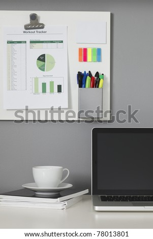 White office desk, laptop computer and a white magnetic board on a gray wall