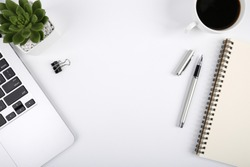 White office desk table with blank notebook, computer keyboard and other office supplies. Top view with copy space, flat lay.