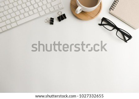 White office desk table with blank notebook, computer, supplies and coffee cup. Top view with copy space. Flat lay.