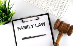 White office desk table with blank sheet with text FAMILY LAW , keyboard and gavel
