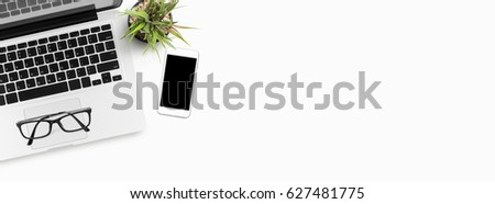 White office desk table with laptop and smartphone. Top view with copy space, flat lay. This can be used to create a website header.
