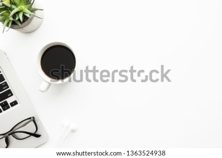 White office desk table with laptop computer, cup of coffee, eye glasses and supplies. Top view with copy space, flat lay. #1363524938