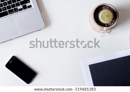 White office desk table with laptop, smartphone, cactus, and glass. Top view with copy space, flat lay.
