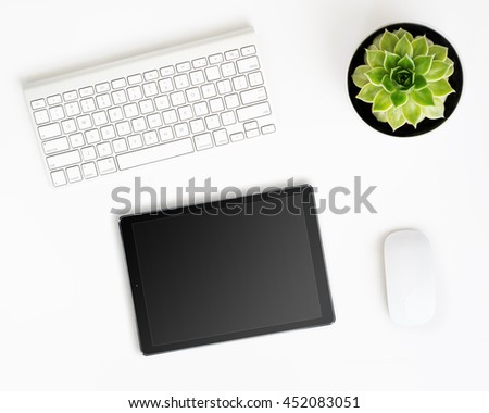 White office desk table with tablet pc computer in ipade style with black screen, wireless aluminum keyboard, mouse and succulent flower in pot. Top view with copy space. Flat lay.