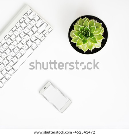 White office desk table with wireless aluminum keyboard, smart phone in iphon style with blank screen and succulent flower in pot. Top view with copy space. Flat lay.