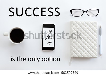 """White office desk with glasses, mobile phone, coffee and pen on it. Lady office supply. Top view. Motivational text """"Success is the only option"""""""