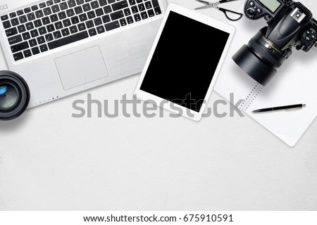 White office photography desk table with laptop, tablet, camera and glass. Top view with copy space