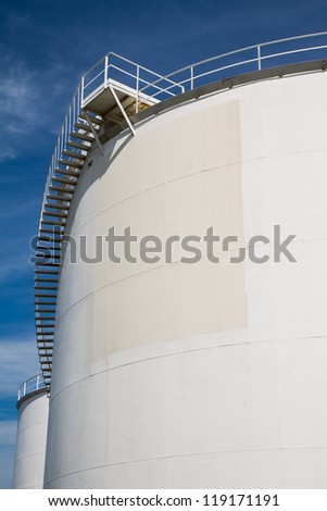 White oil container against a blue sky
