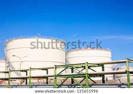 White oil reservoir. Oil and gas refinery plant. Industrial scene of oil field. Oil industry and blue sky