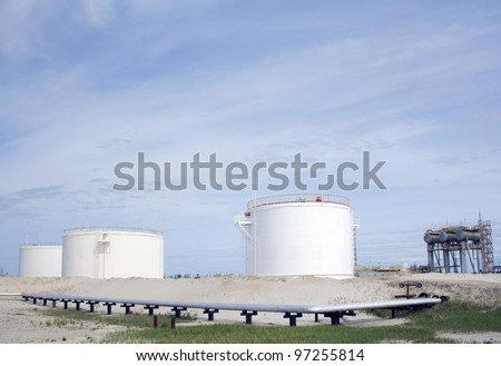 White oil reservoir. Oil and gas refinery plant. Industrial scene of oil field. Oil industry. Blue sky above grey sand.
