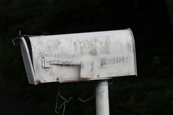 white old and rusty mailbox with faded letters