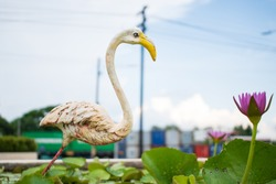 white old bird sculpture in the green lily and pink pond