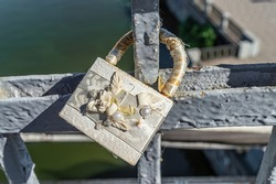 White old weathered closed love padlock with flower and pearl decoration hanging on bridge above river. Love concept.