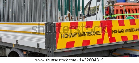 White open bed truck with yellow and red diagonal Highway Maintenance signage is stacked with metal and orange plastic road closure, event crowd control or diversion barriers.