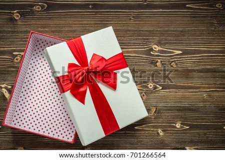 White open new year or Christmas gift box with red ribbon for holiday concept on brown wooden board. Top view with empty space for text and design. #701266564