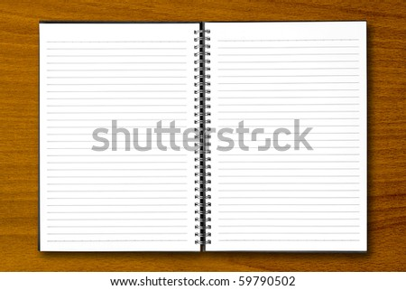 White open notebook on beech wood background.