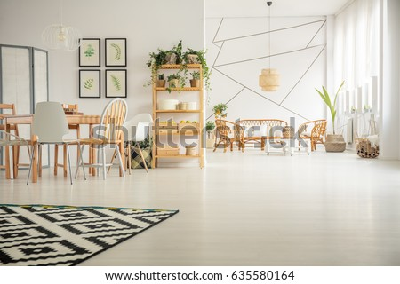 White, open plan home interior with table, chair, pattern carpet