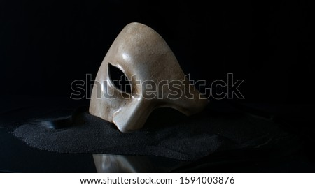 Photo of  white opera mask with sand and cloth