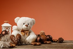 White or light brown adorable teddy bear with christmas decorations and gifts. Holiday concept with toy plush bear and christmass gifts on the wood table.