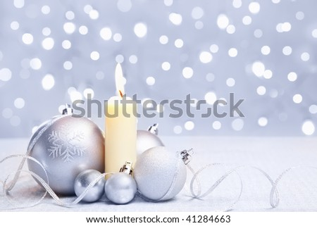 White or silver Christmas ornament and a candle with blur light background
