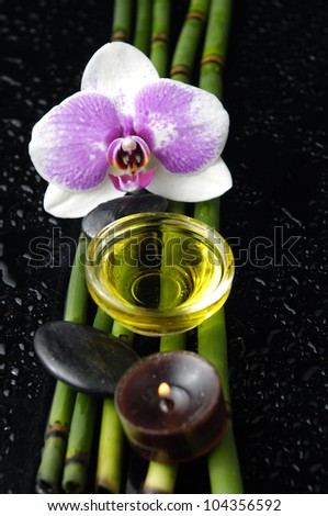 white orchid and bamboo grove ,zen stone ,massage oil, on wet black background
