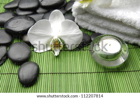 White orchid and stones with towel ,candle on mat