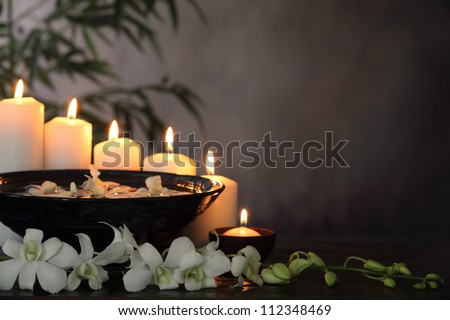 White orchid flower, burning candle and bamboo leaves on grunge background,Zen concept.