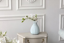 White orchid flowers in vase on table. vintage vase with orchid at home on chest of drawers.