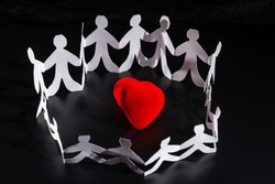 White origami people are staying around red bright heart. International Human Solidarity Day