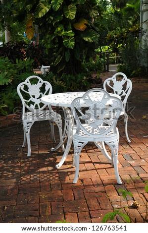 white ornamental garden chairs in a backyard patio with surrounding garden