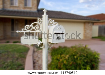 white ornamental Letter box with a facility to write house number and a newspaper holder in front of a beautiful house
