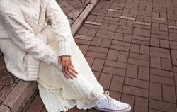 white oversized sweater, light skirt and white sneakers. Details of women's street-style clothing.