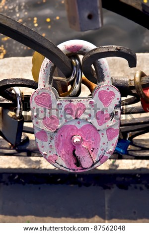 White padlock with painted pink hearts on a close-up on the fence on the background of other castles, water, concrete fences