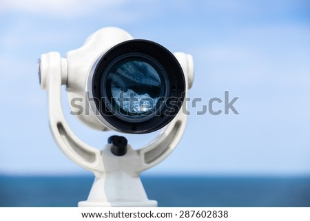 White paid telescope stands on sea coast over blue sky background