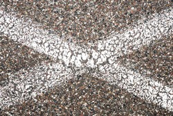 White paint lines in X shape. Lines crossing on grunge asphalt structure. Closeup granular noise background. Street grain pattern. Cracked paint stipe. Marked parking lot point texture.