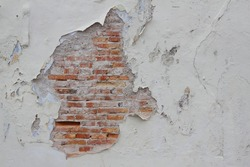White paint on the wall peeling away exposing brick behind it. Conceptual. Vintage.