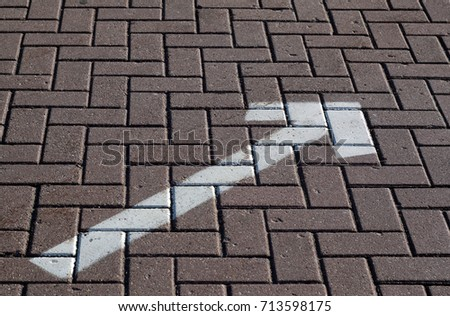 White painted arrow on pavement. Signs and symbols. #713598175