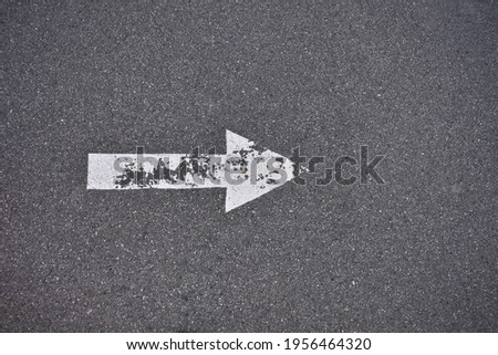 White painted arrow on pavement, weathered and worn white paint. Pointing to the right. Stock photo ©
